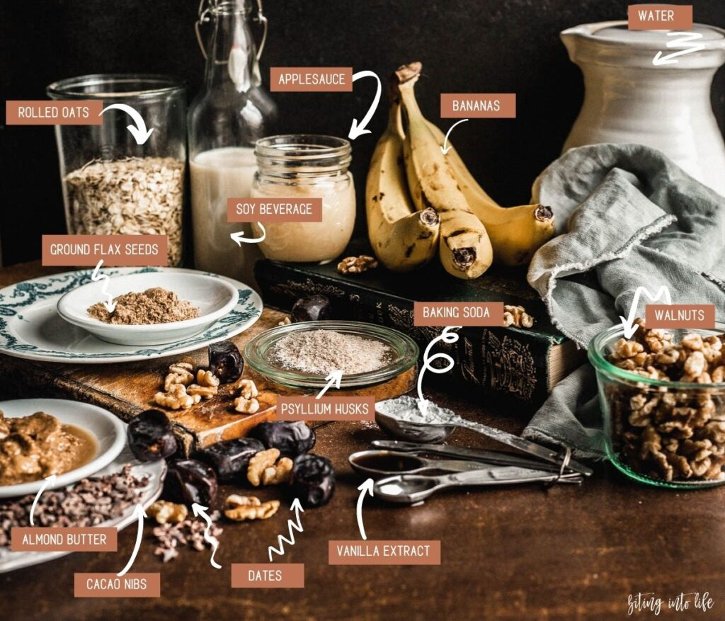 Banana bread Ingredients (clockwise): cocoa nibs and almond butter on small plates, ground flax seeds on a small plate, rolled oat in a glass jar, soy beverage in a small bottle, applesauce in a small glass jar and three bananas placed on a thick book, walnuts in a jar, baking powder and vanilla extract in a set of spoons, psyllium husks on a glass lid, and dates and scattered walnuts