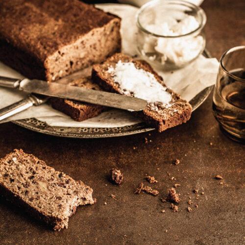 Tranche de pain aux bananes gisant sur un comptoir et placé devant la préparation au complet et quelques tranches tartinées de beurre