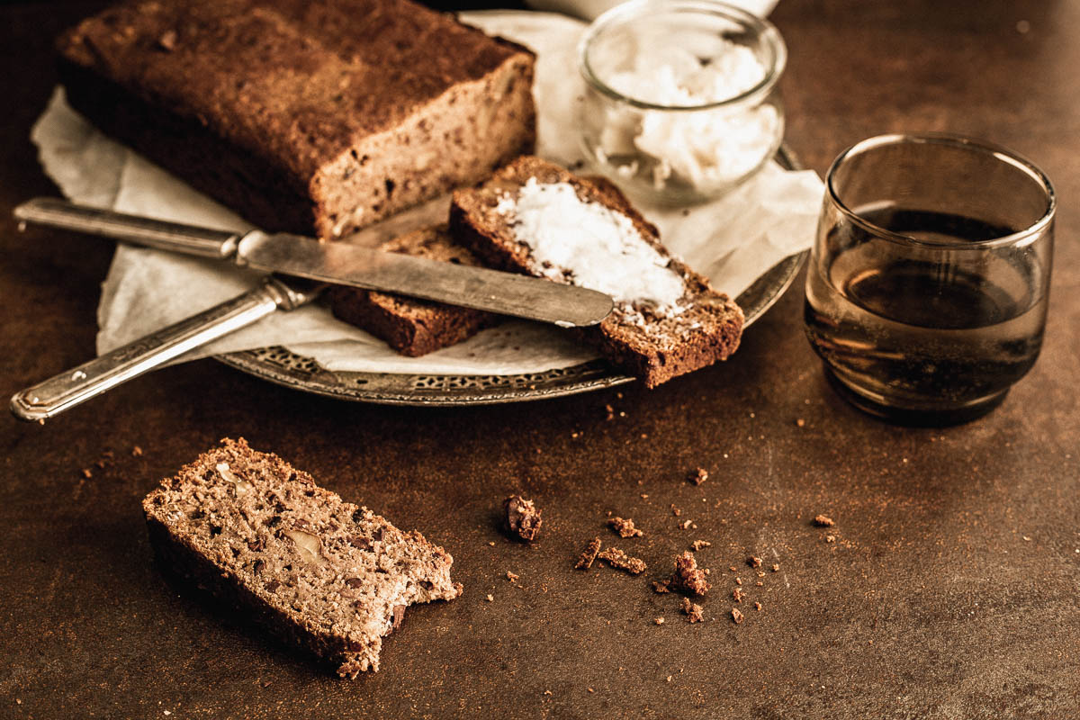 Slice of banana bread lying on a counter and placed in front of the whole preparation and a few slices spread with butter