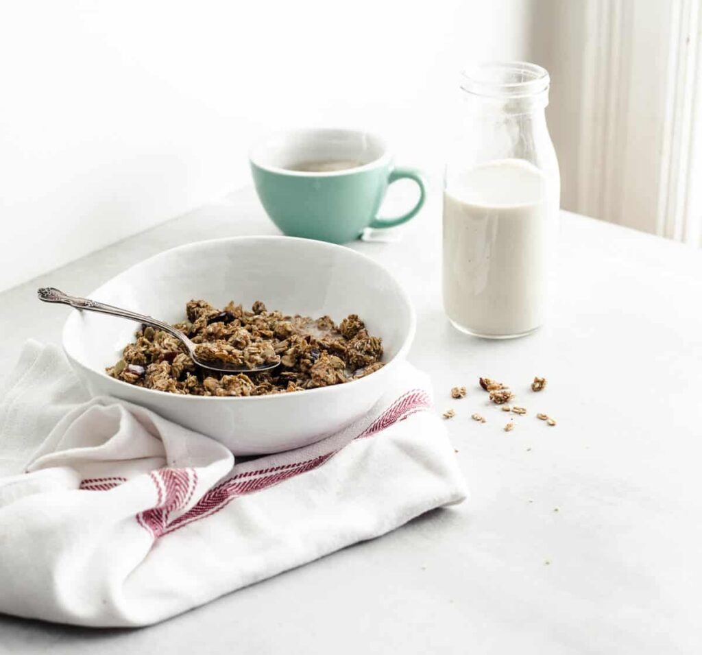A bowl of granola on a white counter accompanied by a small bottle of soy beverage and a cup of tea