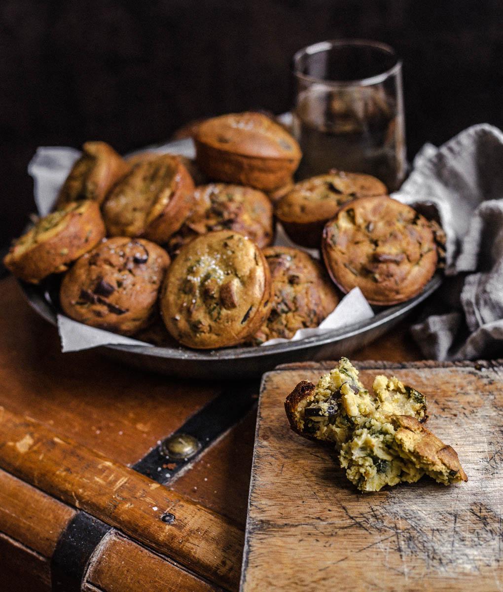 Lot de muffins salés dans dans une assiette métallique reposant sur un coffre en bois.