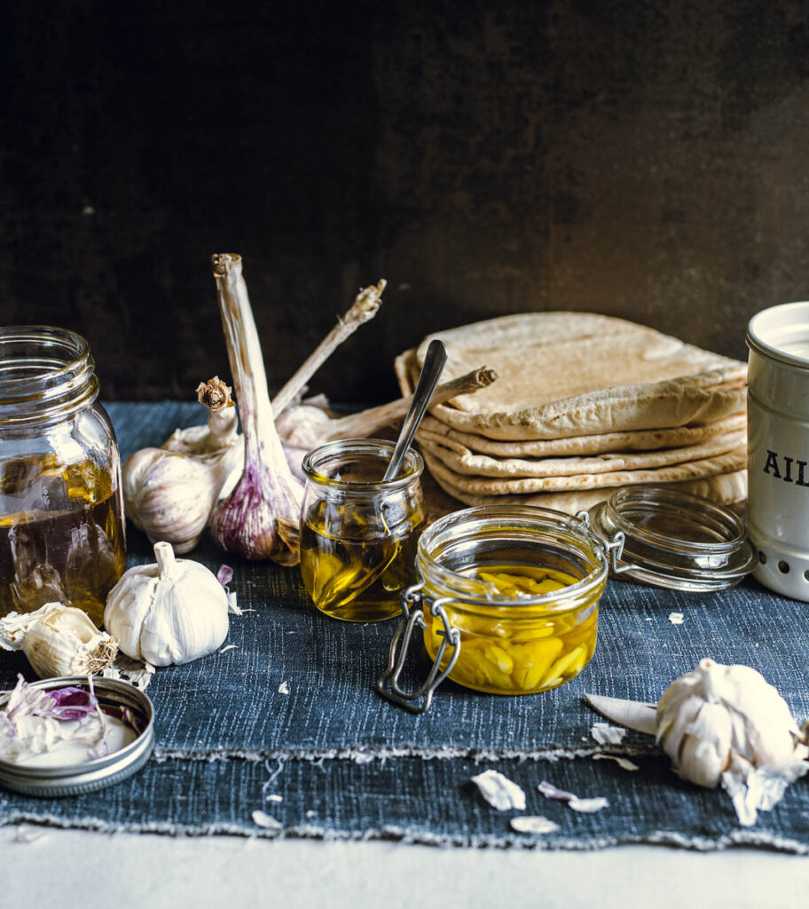 Three small glass jars of garlic-infused oil, surrounded by decorative garlic bulbs, one of which contains garlic cloves cut in half and the others have only the oil