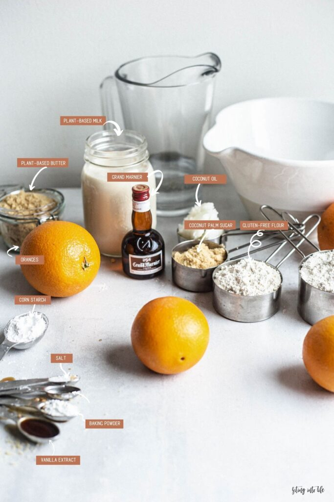 Aesthetically placed crêpe Suzette ingredients (clockwise): oranges, plant-based milk, Grand Marnier, coconut oil, coconut palm sugar, gluten-free flour, salt, baking powder, and vanilla extract