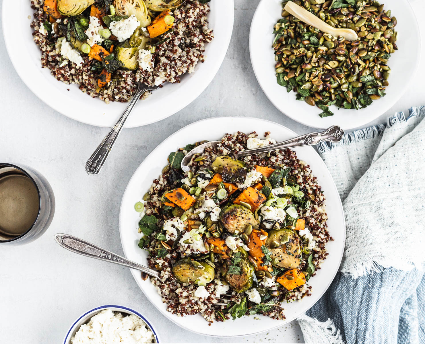A plate of quinoa, Brussels sprouts, and sweet potato mixed with vegetable ricotta-style cheese