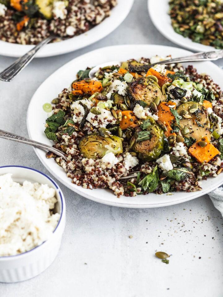 Un bol de quinoa, choux de Bruxelles et patate douce mélangés à du fromage de style ricotta aux légumes