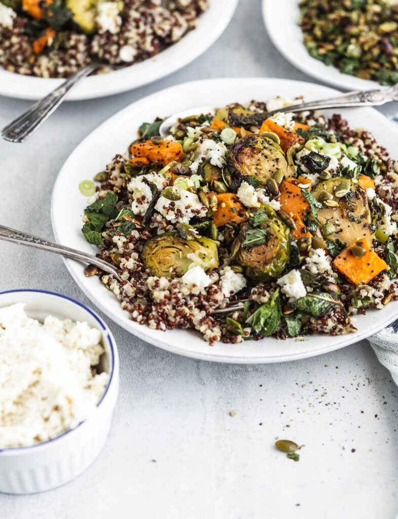 A bowl of quinoa, Brussels sprouts, and sweet potato mixed with vegetable ricotta-style cheese