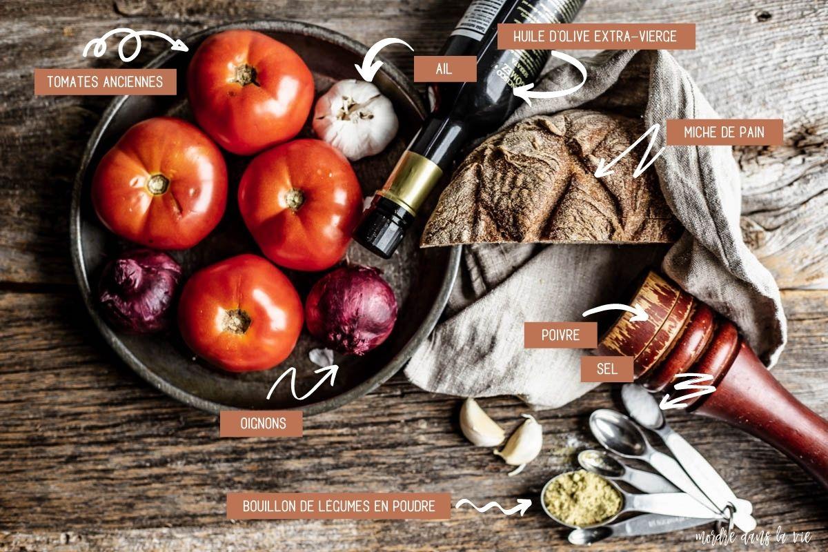 Vue aérienne des ingrédients pour la pappa al pomodoro (dans le sens horaire d'une montre) : tomates, ail, oignons rouges dans un bol métallique avec à leur droite une bouteille d'huile d'olive, une moitié de miche de pain de campagne, un poivrier et un jeu de cuillères à mesurer avec du bouillon de légumes en poudre et du sel