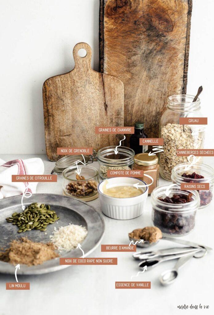 Ingrédients granola végétaliens (dans le sens des aiguilles d'une montre) : plat métallique contenant des graines de citrouille, des flocons de noix de coco râpés non sucrés à côté de nombreux petits pots de noix, du chanvre, de la cannelle en poudre, des flocons d'avoine, des canneberges, de la compote de pommes et un ensemble de cuillères à mesurer contenant du beurre d'amande et de l'extrait de vanille