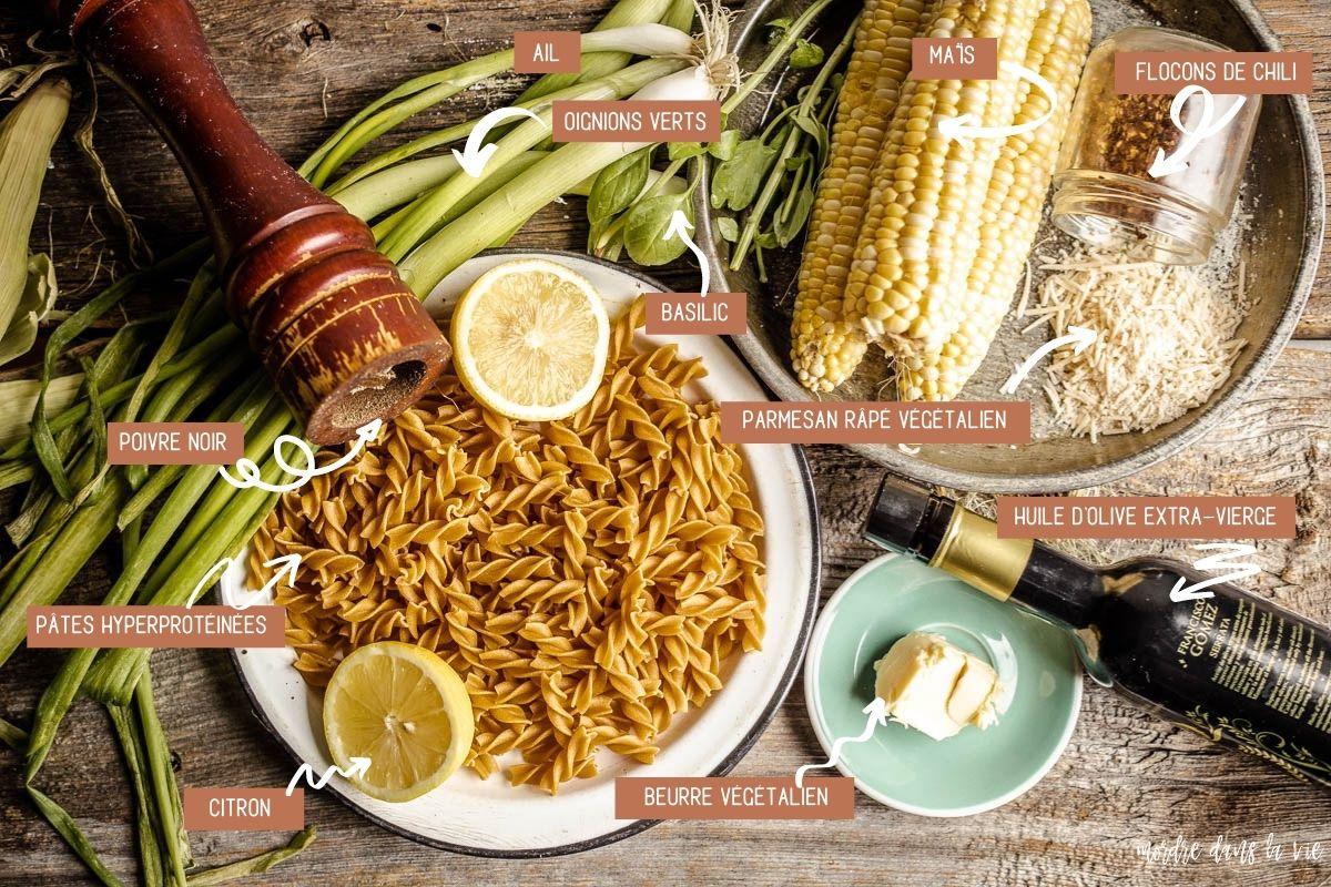 Vue aérienne des ingrédients pour faire les pâtes au maïs crémeux reposant sur une planche de bois (dans le sens d'une aiguille d'une montre) : poivrier sur des oignons verts, basilic frais, trois épis de maïs, flocons de chili en pot, parmesan végétalien dans une assiette métallique, bouteille d'huile d'olive extra-vierge, morceau de beurre sur une petite assiette vert pâle, fusilli sec avec deux moitiés de citrons dans une assiette en émail