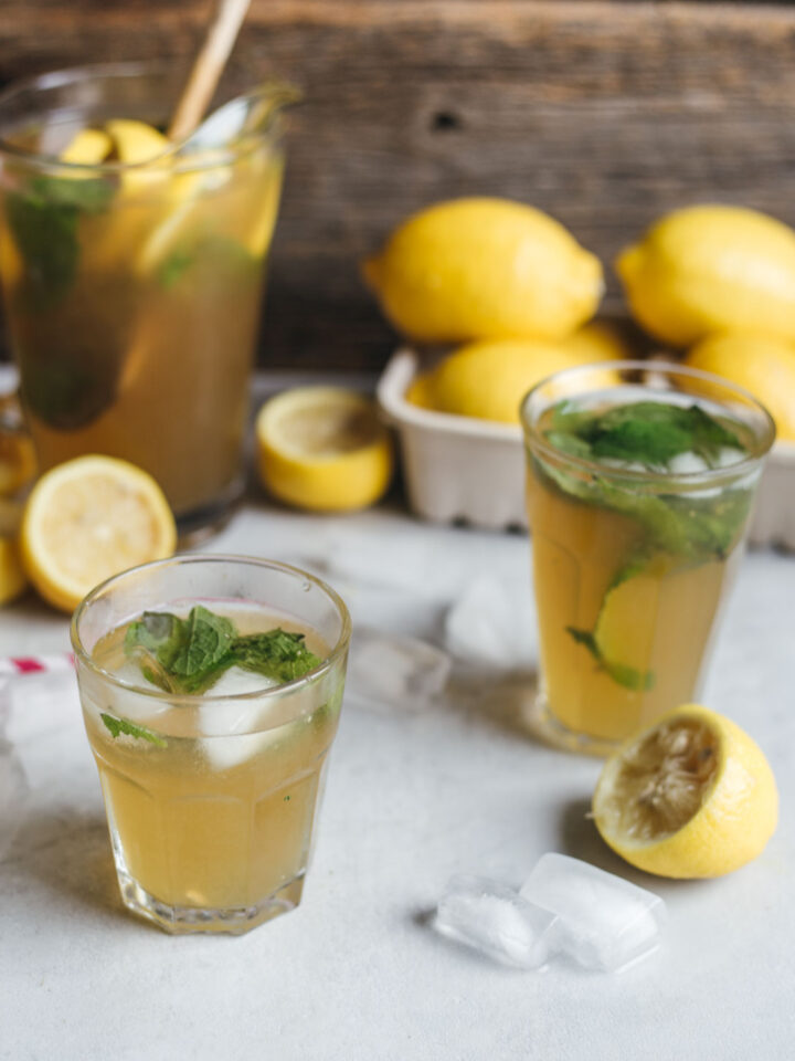 Two glasses of lemonade garnished with mint on a surface