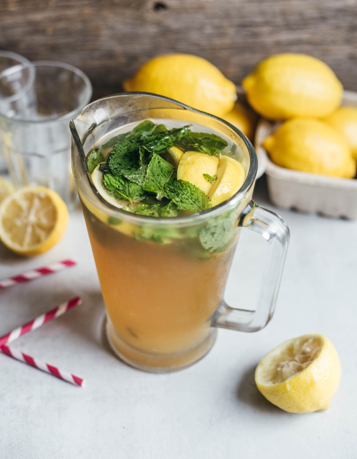 Mint leaves dipped in a glass pitcher of lemonade