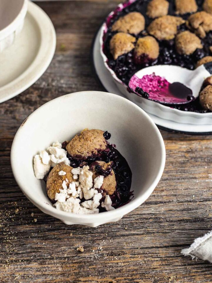 Blueberry cobbler topped with ice cream in a bowl with baking pan in the back